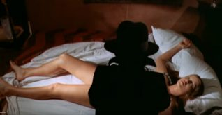 A screenshot taken from The Black Belly of the Tarantula (1971).  It shows a dark figure hovering over a woman who is laying in her bed.
