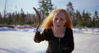 A screen shot taken from the 1983 horror film Curtains. It shows a woman in an old lady mask brandishing a scythe.
