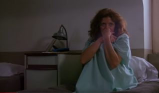 A screen shot taken from the 1983 horror film Curtains. It shows a woman sitting on a bed in a hospital gown.