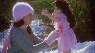 A screen shot taken from the 1983 horror film Curtains. It shows a woman holding a doll in the snow.