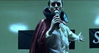 A screenshot taken from the 2004 horror film Calvaire. It shows a man in a cape singing.