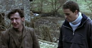 A screenshot taken from the 2004 horror film Calvaire. It shows one man talking to another. The one on the left looks distressed.