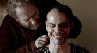 A screenshot taken from the 2004 film Calvaire. It shows a man crying in a dress, while another shaves his head.