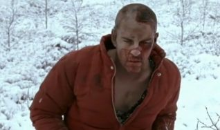 A screenshot taken from the 2004 horror film Calvaire. It shows a bloodied man hobbling through the snow.
